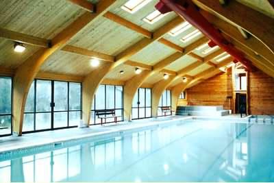 A log swimming pool enclosure provides a wonderful atmosphere