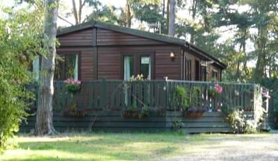 Mobile log cabin installation looks much better with service pipes covered over!