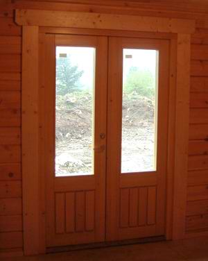 A french style of external timber doors inside a log cabin